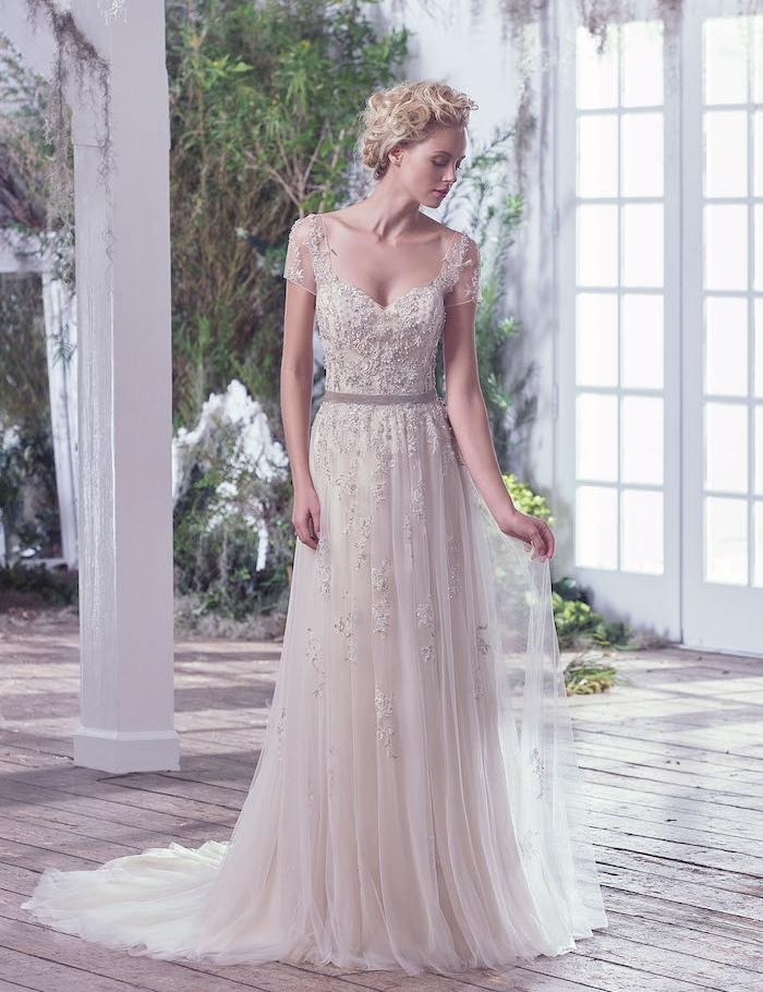 exemple de robe de mariée champetre avec un bustier décoré de pierres avec bretelles et jupe en tulle avec motifs brodés