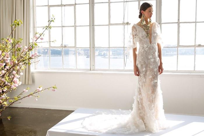 rone de mariée bohèmecoupe droite avec longue traine, manches et décoration de plumes, col en v, collier et boucles d oreille à motifs floraux