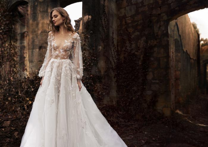 robe de mariée haute couture avec des manches transparentes et des plumes décoratifs, jupe voile transparente, coupe évasée
