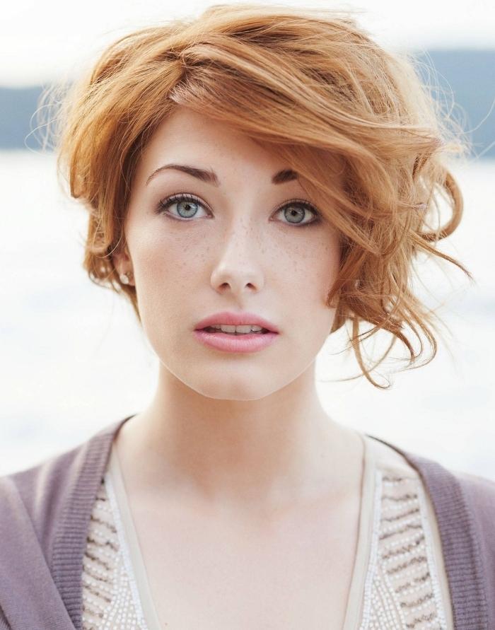 jolie femme au visage clair et yeux verts avec une coupe de cheveux courte dégradée en carré flou cuivrée