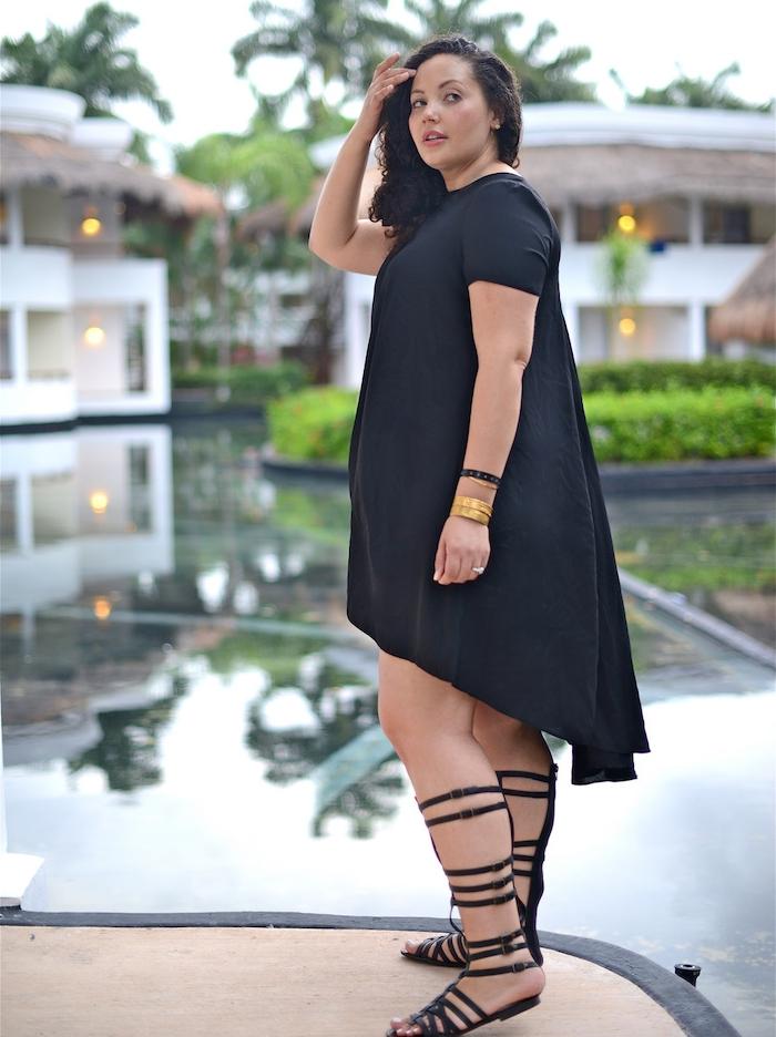 idée de robe pour femme ronde couleur noire et sandales femme noires style grec, cheveux bouclés sur le coté, bracelet or