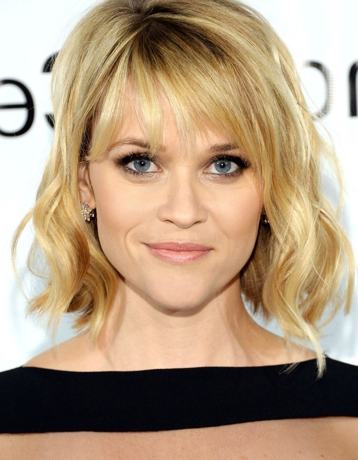 coiffure de Reese Witherspoon en cheveux mi-longs bouclés de couleur blonde avec racines foncées et frange longue