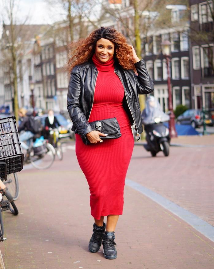 robe rouge femme afro avec col, veste en cuir noir, chaussures de sport, cheveux bouclés, pochette noire, motif crane