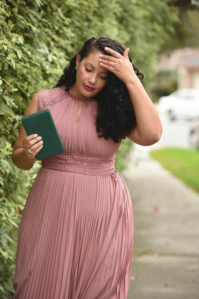 robe plissée, ceinture à la taille, robe sans manches, cheveux noirs frisés, broderies discrètes