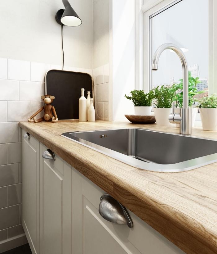 décoration de cuisine aux murs blancs avec revêtement partiel en carrelage blanc et plan de travail stratifié bois