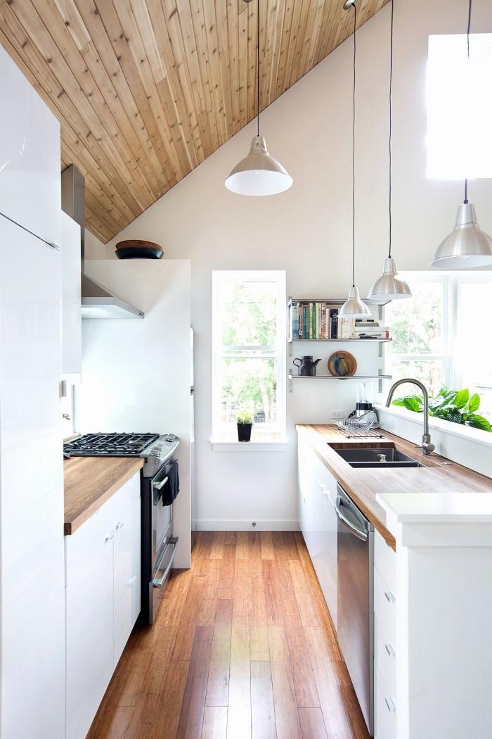 style minimaliste dans une cuisine aux murs blancs avec revêtement de plafond et de plancher en bois et éclairage industriel