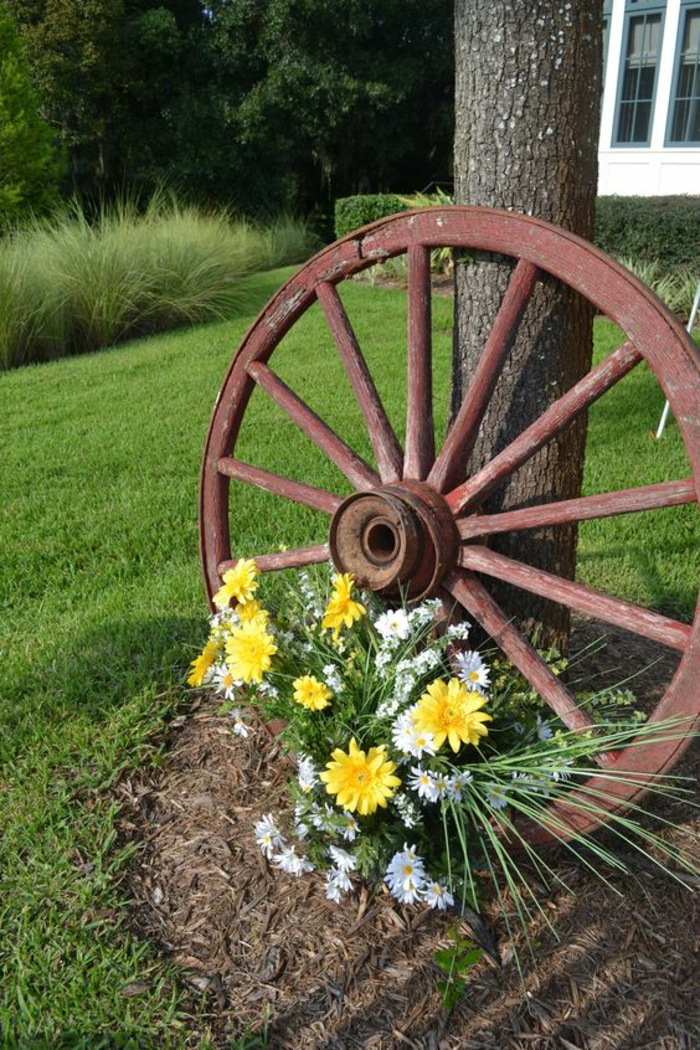 élément décoratif, grande roue de chariot appuyée contre un arbre, decorer son jardin, jardin paysager, amenagement exterieur, fleurs printanières a la base de la roue