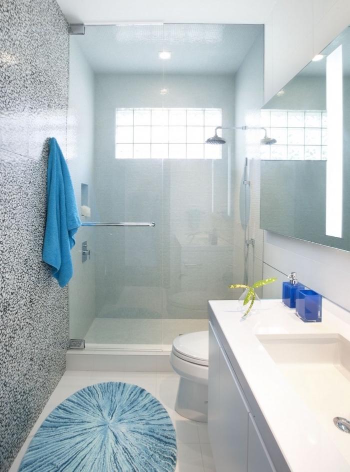 salle de bains en longueur blanche et bleue rénovée avec grande douche vitrée