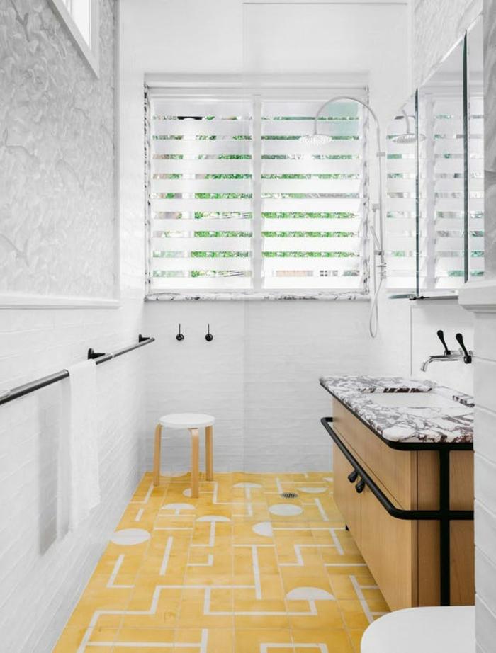 decoration murale design en blanc pour le bain, sol en carrelage jaune et blanc aux motifs graphiques, petit tabouret rond en blanc avec des pieds en méta jaune, meuble évier avec plan surface imitation marbre en noir et blanc
