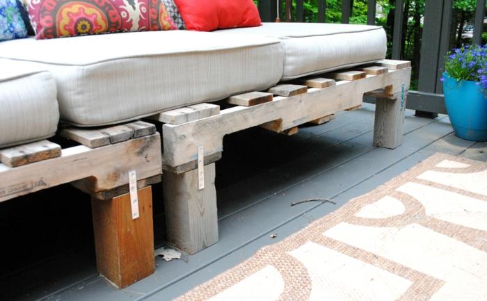 fauteuil palette, canapé palette, table de jardin en palette, tapis en beige, banc en palette, coussins en couleur ivoire, coussins en rouge, fuchsia et bleu marine