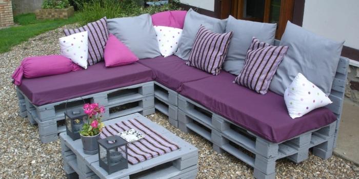 canapé en palette, fauteuil palette, meubles peints en gris perle, coussins en gris et fuchsia, table basse en gris avec couverture aux rayures en fuchsia et prune