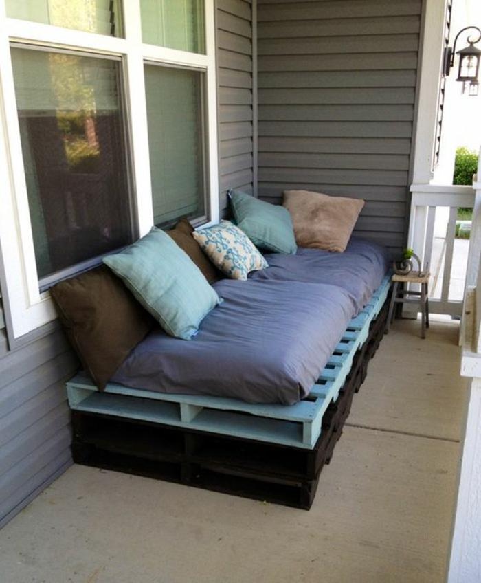 canapé palette, peint en noir et en bleu pastel, matelas en bleu indigo, coussins en marron, vert menthe et beige, salon de jardin en palette