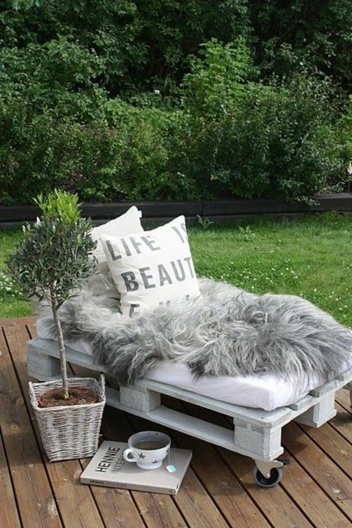 chaise-longue en palettes avec des roues, bois peint en blanc, plante verte-arbrisseau dans un pot marron posé dans une porte-plant en osier tressé peint en blanc , fauteuil palette