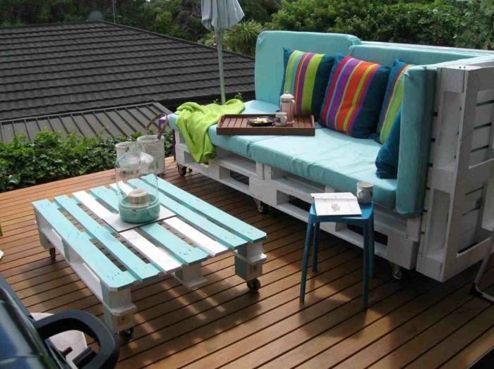 table de jardin en palette, fauteuil palette, canapé palette, meuble recouvert de matelas en vert réséda, coussins aux couleurs et aux motifs ethniques, tabouret en plastique en bleu pastel, table basse en bleu pastel et blanc avec des roues noirs