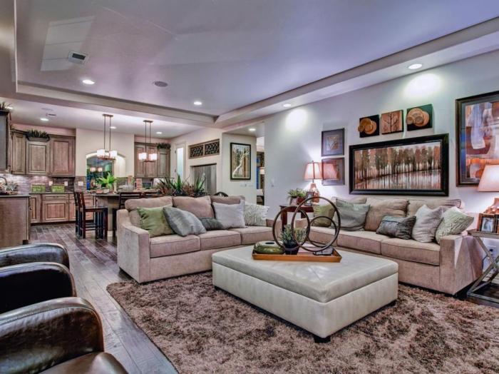 couleur tendance salon avec un grand tapis rose nude, table basse pouf, canapé d'angle rose et espace dînatoire