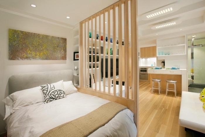 chambre à coucher avec grand lit et séparation de bois dans un studio aménagé en blanc et noir avec petite cuisine