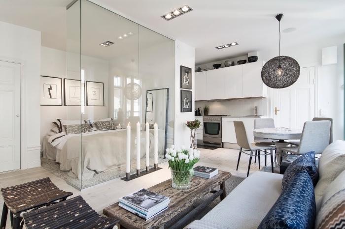 design intérieur moderne dans un studio blanc avec salon cuisine salle à manger et coin à dormir séparé avec vitrage