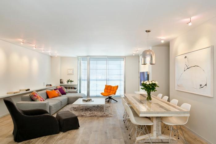 choisir une peinture tendance salon, sofa gris moderne, fauteuil noir, table en bois et chaises scandinaves