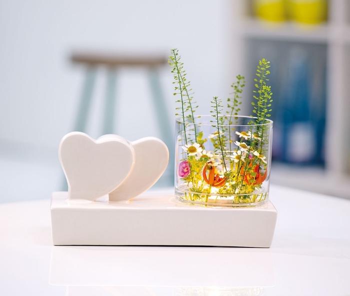 objet de décoration avec support blanc et petits coeurs combinés avec un récipient en verre et plantes vertes