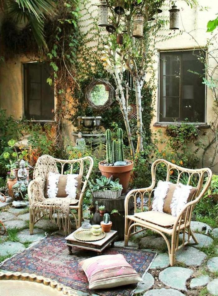 aménagement de jardin en style boho chic avec deux fauteuils en rotin aux dossiers larges, tapis oriental, grand pot avec des cactus