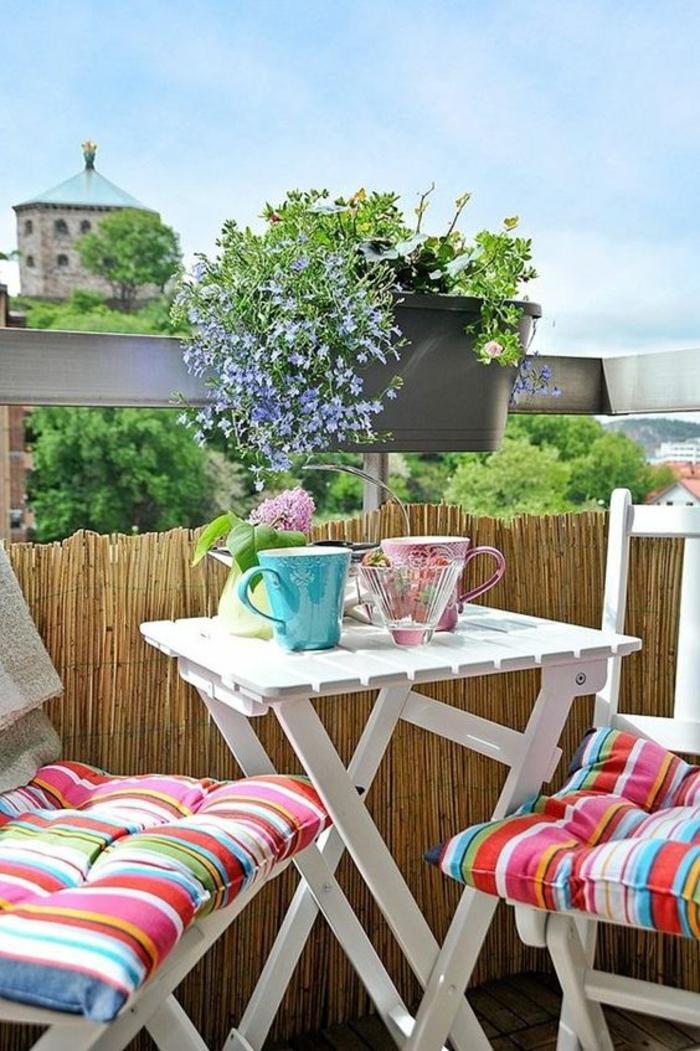 balcon fleuri, idée déco terrasse, chaises et table pliable en bois blanc PVC, garde-corps recouvert de bambou pour préserver l'intimité, coussins meubles aux rayures verticales en couleurs vitaminées