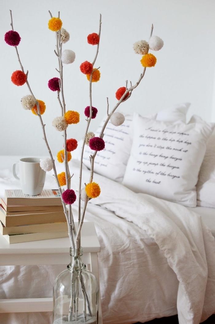 idée déco chambre à coucher blanche avec meubles de bois et une vase en verre avec bouquet de branche séchée décoré de pompons