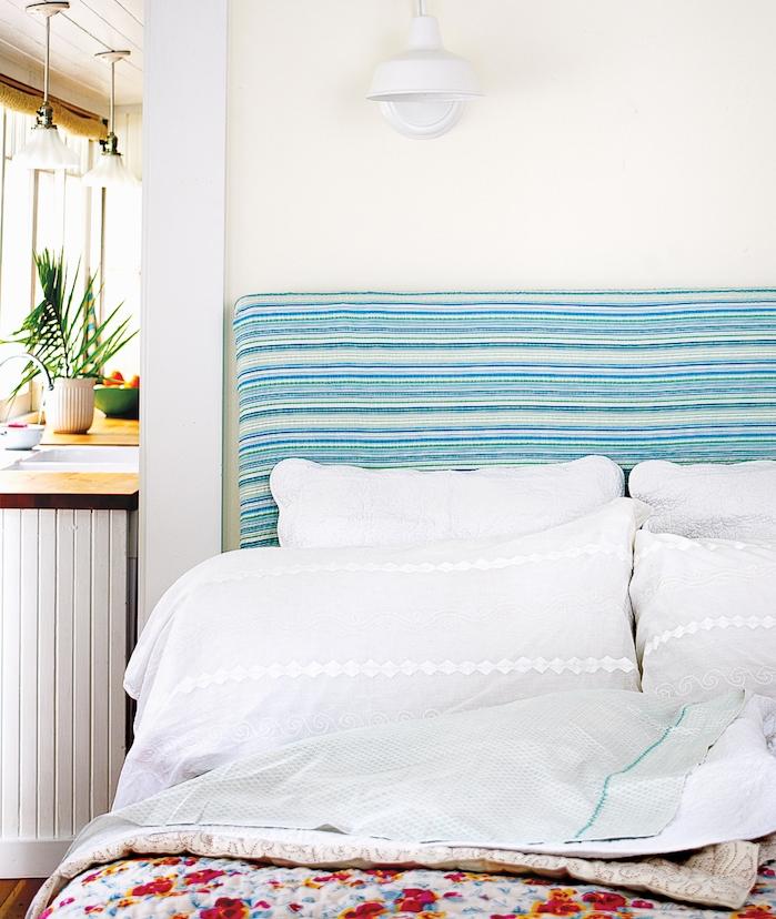 tete de lit design à rayures bleu et blanc, linge de lit blanc et couverture de lit fleurie dans un chambre à coucher ouverte