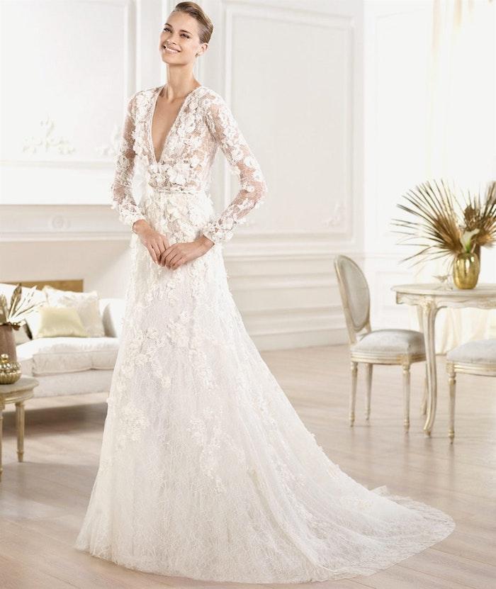 robe de mariée originale en dentelle avec traine et des fleurs brodées, manches longues, col en v