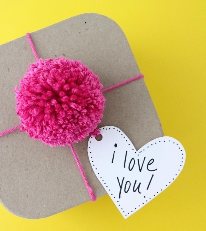 comment emballer un cadeau surprise avec fil et boule de laine de couleur rose fuschia, message mot doux je t'aime