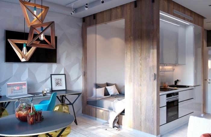 exemple comment aménager un studio avec cube multifonction en bois pour y encastrer un grand lit et une petite cuisine