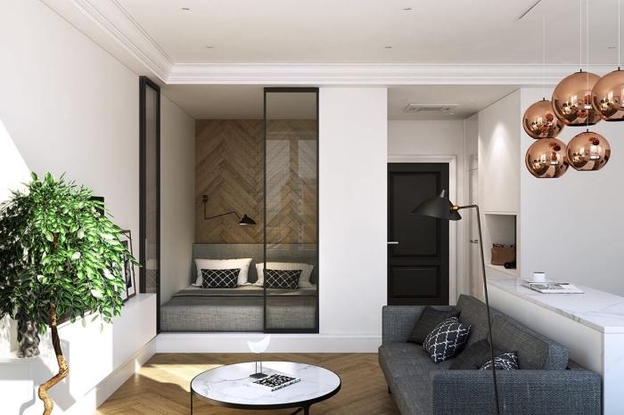 style moderne aux couleurs neutres avec canapé gris anthracite et table ronde à design marbre blanc dans le salon