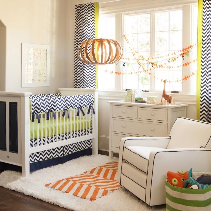 aménagement chambre enfant aux murs beige et plancher de bois foncé avec coussins et rideaux en blanc et bleu marine