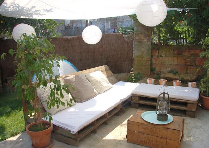 comment fabriquer un canapé en palette soi-même coussin d assise blanc et coussins décoratifs gris et beige, table basse cagette de bois, voile d ombrage
