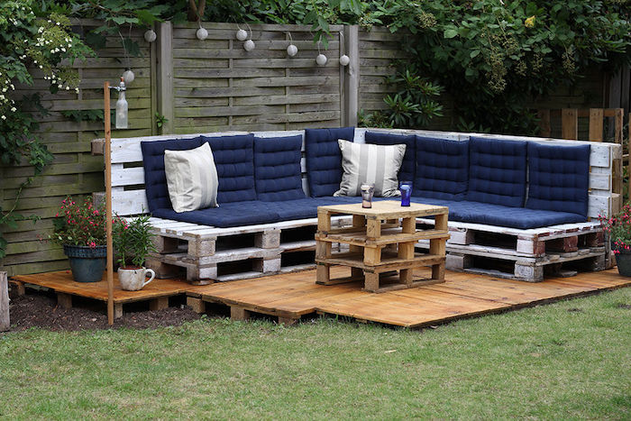 meubles de jardin en palettes avec canapé d angle repeint en blanc et table basse palette sur une terrasse exterieure en bois