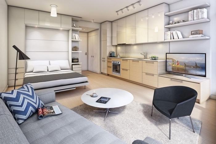 modèle de lit escamotable pour gagner place dans aménagement petit appartement avec petite cuisine et salon en blanc et beige