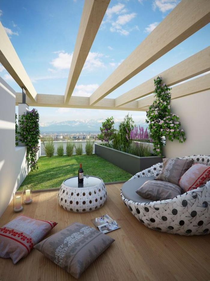 decoration jardin terrasse, decoration terrasse exterieur, pergola avec des poutres en beige, sol recouvert de bois clair, meubles en rotin blanc, table ronde et grand fauteuil canapé rond avec trois grands coussins en style oriental