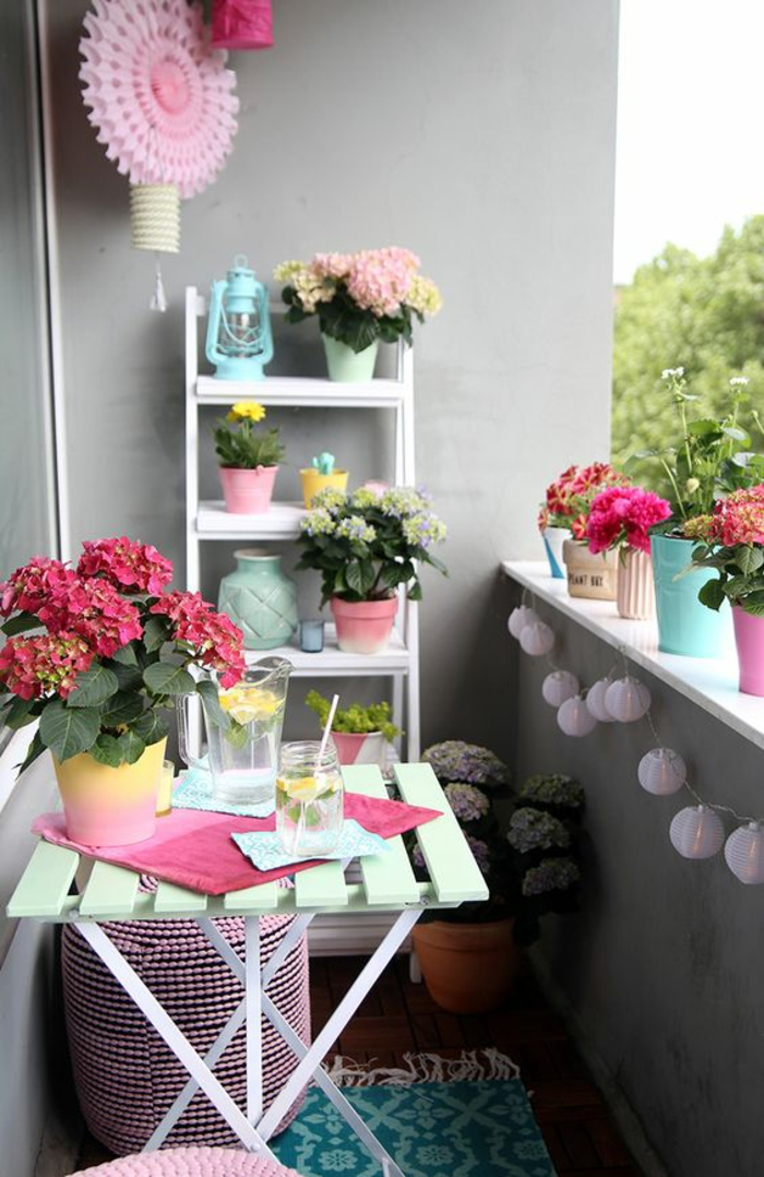 ambiance gaie, idee amenagement terrasse avec beaucoup de couleurs, fleur en carton rose, étagères blanches avec des pots en couleurs pastels, table en bois couleur vert menthe, tapis en vert avec des motifs arabesques, guirlande de lanternes blanches chinoises
