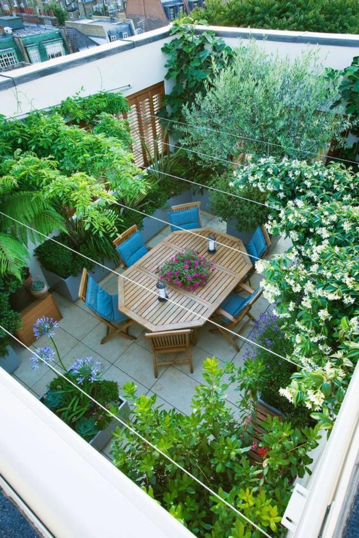 six chaises en bois clair et tissu bleu turquoise et grande table hexagonale, decoration jardin terrasse, arbres verts et plantes en fleurs, dalles en carrelage blanc