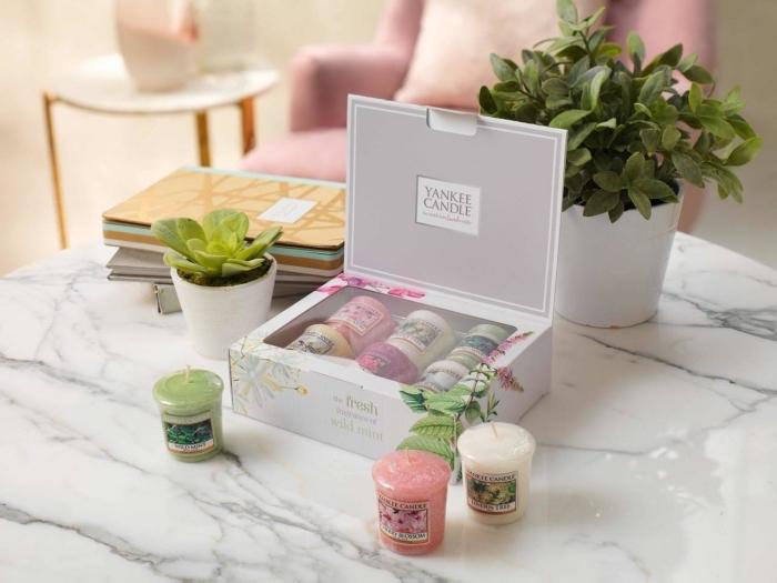 collection de bougies aromatiques de couleurs variées dans une boîte grise à design style pour cadeau femme parfait