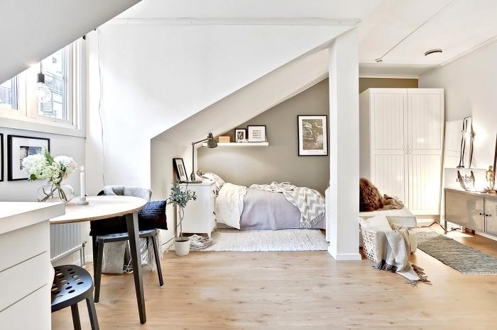 exemple d'aménagement sous pente dans un petit studio avec coin intime et bureau aux murs blancs et plancher de bois