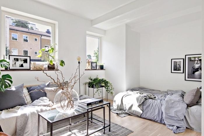décoration appartement étudiant aux murs blancs avec accessoires cozy en forme de coussins et plaids gris et beige