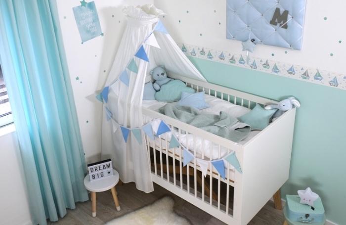 design bicolore en blanc et bleu pastel dans une pièce bébé avec lit en blanc et plancher de bois stratifié foncé