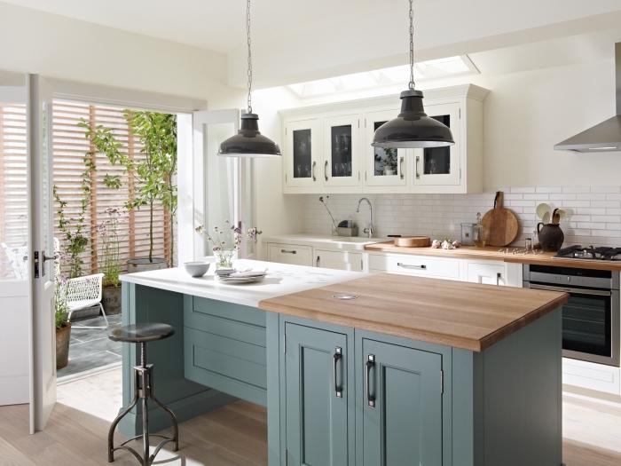 cuisine bien équipée avec plan de travail ilot central avec armoires en vert foncé pastel et comptoirs blanc et bois stratifié