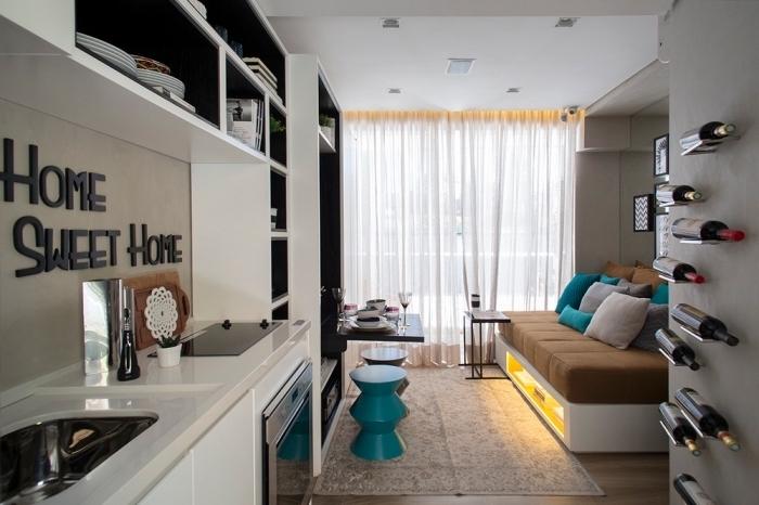 aménager un petit appartement avec cuisine en blanc noir et salon avec canapé escamotable à rangements