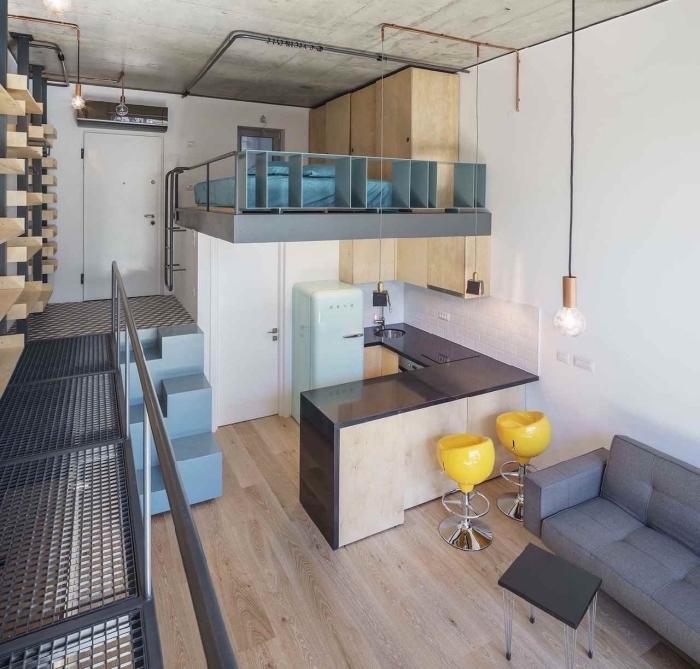 déco de style loft industriel avec plafond à design béton et tuyaux apparents dans un studio étudiant avec petite cuisine d'angle