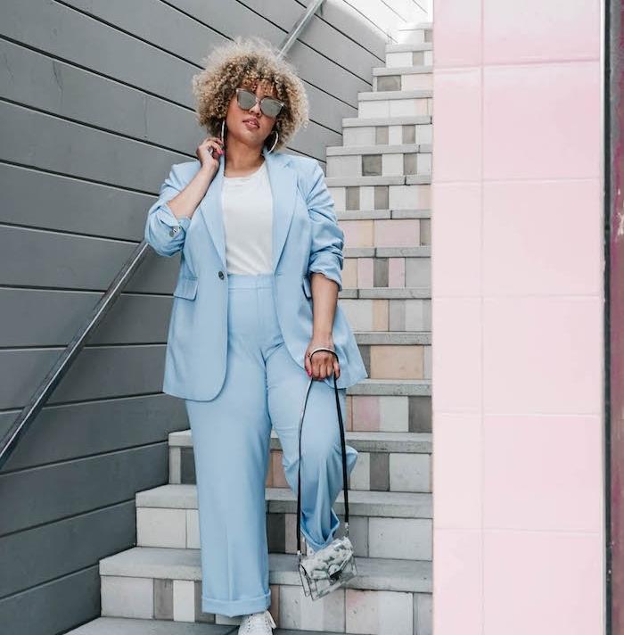 pantalon et veste bleu ciel, tee shirt blanc, petit sac à main effet marbre, lunettes de soleil, cheveux bouclés femme afro