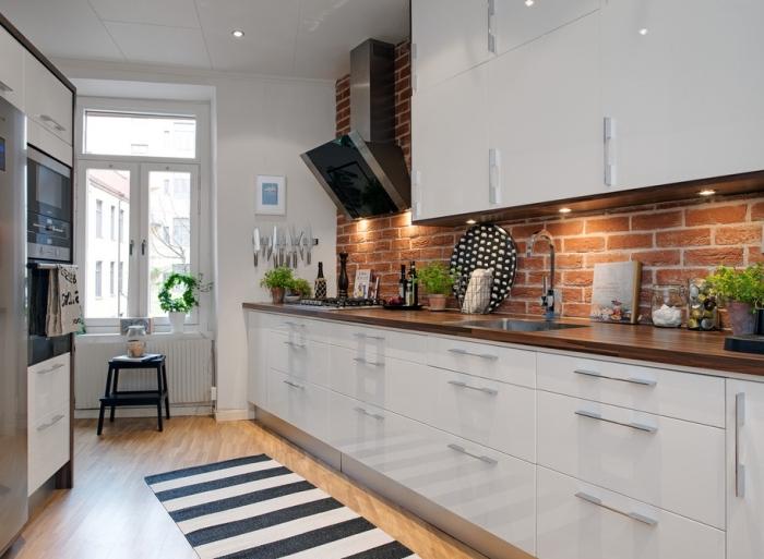 exemple de cuisine blanc laqué aux armoires modernes avec poignées métalliques et comptoir de bois stratifié foncé