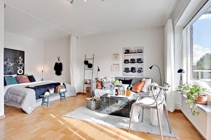exemple aménagement studio 20m2 avec rail de rideaux pour séparer la chambre à coucher du salon blanc