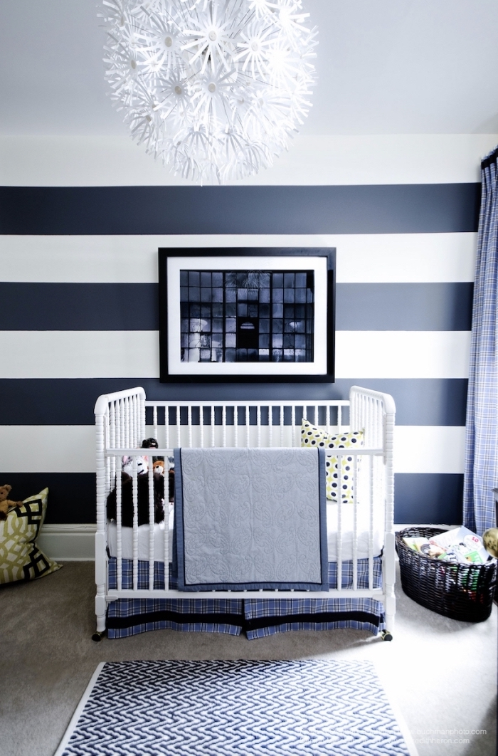 aménagement de pièce enfant moderne avec papier peint design rayé et lustre à design floral pour une déco monochrome en blanc et bleu marine