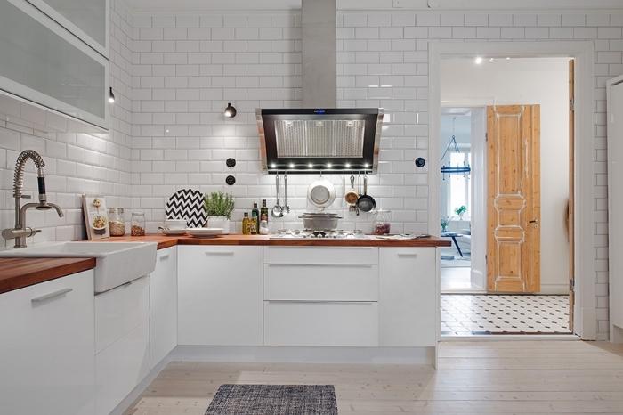 exemple de cuisine blanche avec parquet de bois clair et revêtement mural en carrelage à design briques blanches